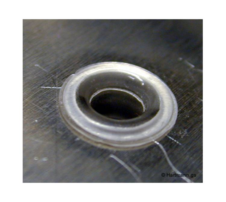 Ein Blech-Stanzteil wird durch einen heißverstemmten Pin in seiner Position fixiert.